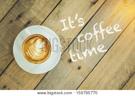 Top view of coffee cup on wooden table with text