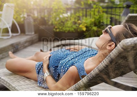 Young Expectant Mother Wearing Sunglasses And Summer Dress Sleeping Or Having Nap On Lounger, Keepin