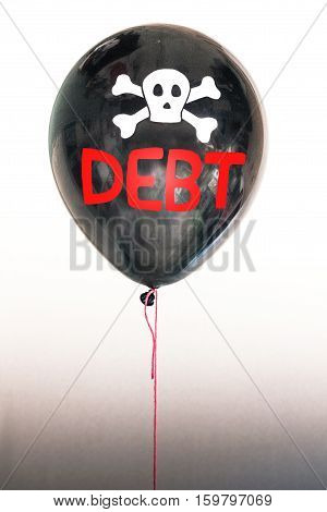 The word debt and a skull and cross bones on a balloon illustrating the concept of a debt bubble, debt default, student loans, auto loans, US, EU and sovereign country  debt.