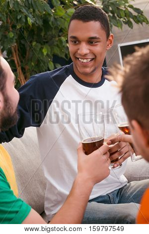 Closeup picture of happy friends drinking beer at home after hard working week or day. Smiling man communicating with his best colleagues.