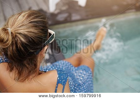 Young Pregnant Woman With Hair Knot And Tanned Skin Sitting On Edge Of Swimming Pool And Splashing L