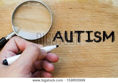 Human hand over wooden background and autism text concept