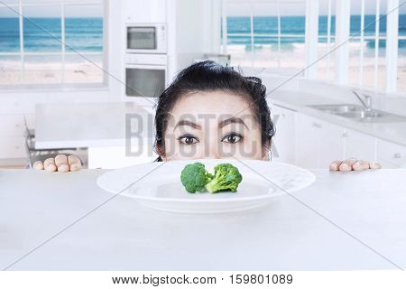 Picture of young woman peeping broccoli on a plate with beach background on the window