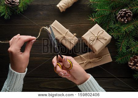 Female hands with scissors cut off the rope, Christmas gifts in kraft paper. Gift box in brown kraft paper tied with string. Christmas gift in kraft paper with decoration on rustic wooden background.