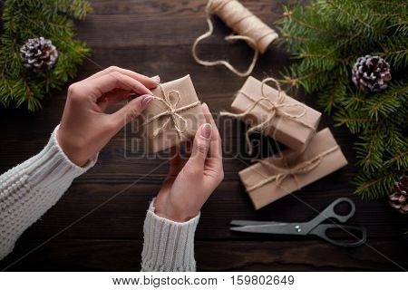Beautiful female hands are packed Christmas gift in brown kraft paper, rope. Gift box in brown kraft paper tied with string. Christmas gift in kraft paper with decoration on rustic wooden background.
