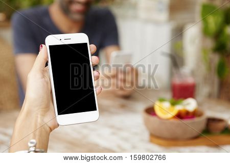 Woman Holding Cell Phone For Reading Or Sending Message, Surfing Internet During Breakfast At Restau