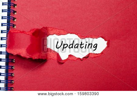 The word updating appearing behind torn paper
