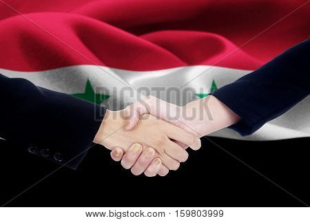 Image of a negotiation handshake with two people hands closing a meeting by shaking hands in front of a national flag of Syria