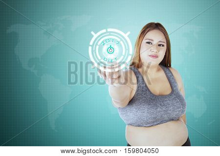 Obese woman click start button with text diet 2017 on the virtual screen