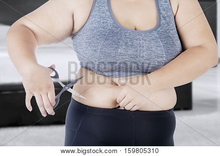 Picture of woman holds her big belly with a scissor while standing at home