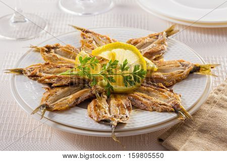 Fried sardine fillets served on a plate with lemon and parsley.