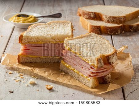 A smoked meat sandwich on a wooden table with mustard.