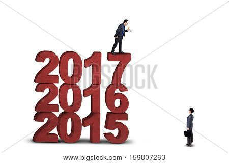 Picture of businessman shouting with a megaphone to talk his partner while standing above numbers 2017 isolated on white background