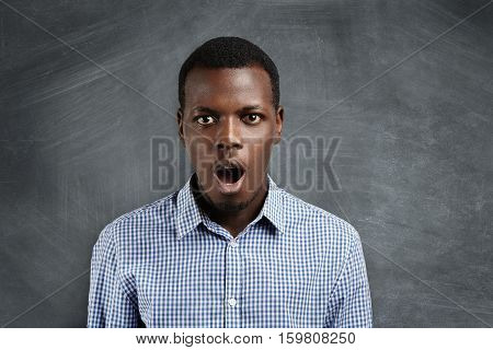 Isolated Shot Of Attractive Young African Customer Looking At Camera In Astonishment And Full Disbel