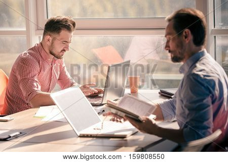 Business people working on laptop computer in board room in office. Serious and confident men working upon business projects for companies, enterprises, firms.