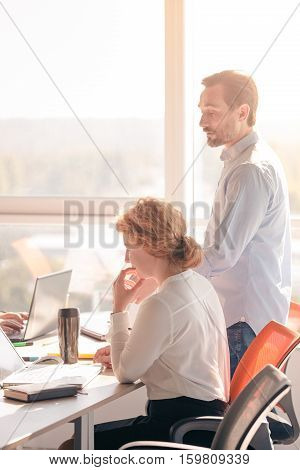 Business people working in board room in office all together. Businessman dictating to his worker woman business plans for future.