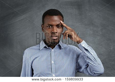 Isolated Shot Of Handsome Frustrated African Man Wearing Shirt Holding Finger On His Forehead As If