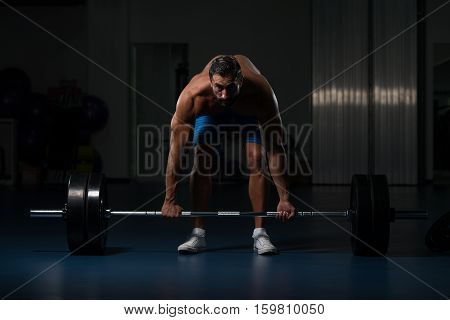 Man In The Gym Exercising Back With Barbell