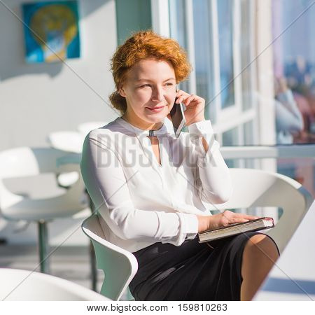 Portrait of red haired businesswoman talking over mobile or smart phone and looking at window while discussing plans for evening with her friends.