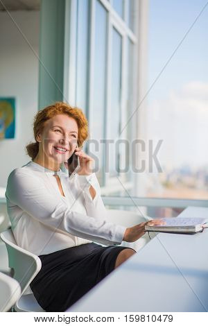 Confident businesswoman talking over mobile or smart phone while having break. Red haired woman looking at window and discussing plans for evening.