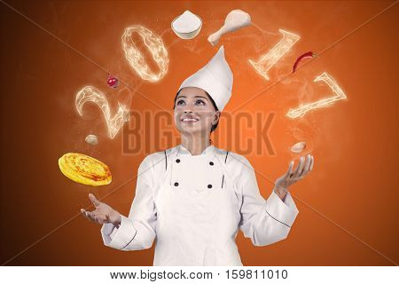 Photo of an Indian magician chef is juggle with ingredients and smoke shaped numbers 2017 in the studio