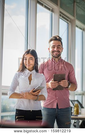 Businessman and businesswoman posing with tablet PCs in office interior. Happy smiling colleagues looking at camera. Office atmosphere. Confidence concept.