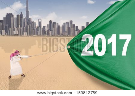 Image of young middle eastern man wearing headscarf and pulling a big banner with numbers 2017 in the desert