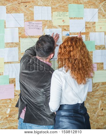 Back view of businessman and businesswoman talking or communicating about new business meeting of Bord or Directors in office interior.