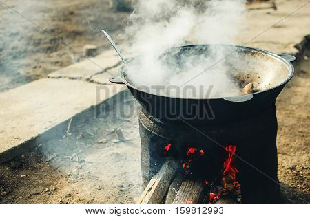 The cauldron on the fire street food cooking pilaf meat picnics holidays