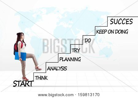 Female high school student walking on the staircase with strategy plan to success and world map background