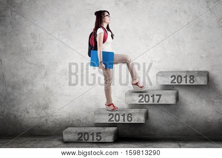 Female college student walking upward on the staircase toward number 2017