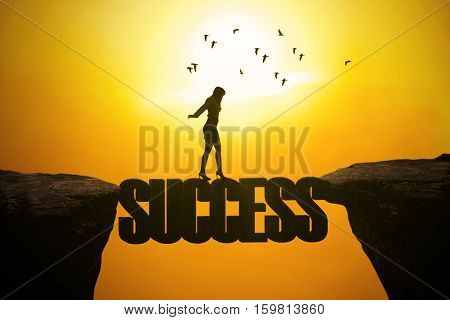 Silhouette of businesswoman walking through a bridge on the mountain with success word