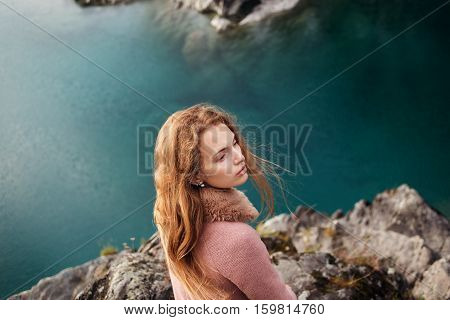Girl in pink coat standing on a promontory above the lake close-up shot