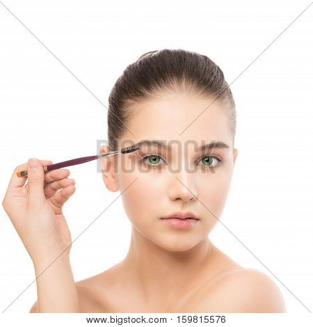 Portrait of beautiful young brunette woman with clean face. Beauty spa model girl with perfect fresh clean skin applying cosmetic brush. Youth and skin care concept. Isolated on a white background.