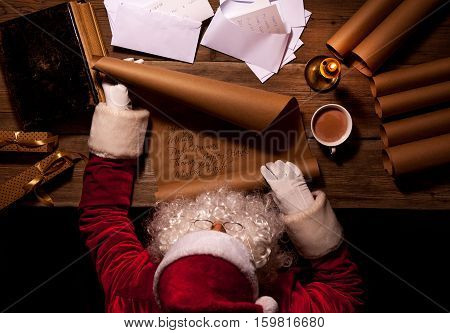 Santa Claus sitting at his room and reading Christmas letter or wish list
