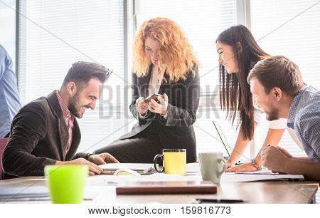 Business people working in team in board room in office. Happy coleagues discussing business criteris for their company, enterprise or firm.
