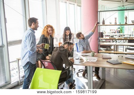 Businessman making photos on mobile or smart phone while working round table in board room in office interior. Colleagues working upon business projects all together.