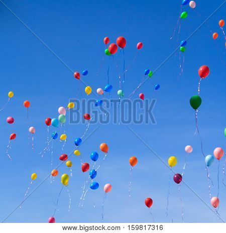 Many bright baloons in the blue sky in Spring