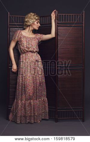 Beautiful blond young woman in dress standing near wooden brown folding screen. Studio shot on black background. Copy space.