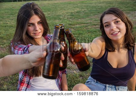 Female friends celebrating the holiday having a good time drinking beer in a park. They are toasting with bottles and wishing each other all goes very well. They're happy.