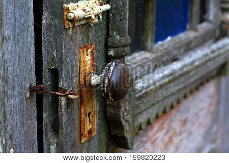 Old out house rusty door knob and latch with decorative old barn wood.
