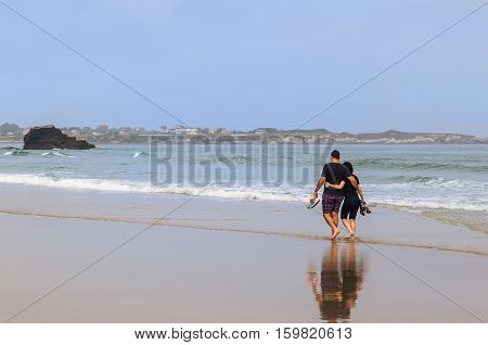 Embraced Couple Strolling On The Beach