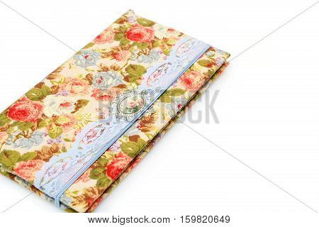 Beautiful handmade scrapbooking holder for travel documents with ribbon closure. Floral fabric design. isolated on white background.