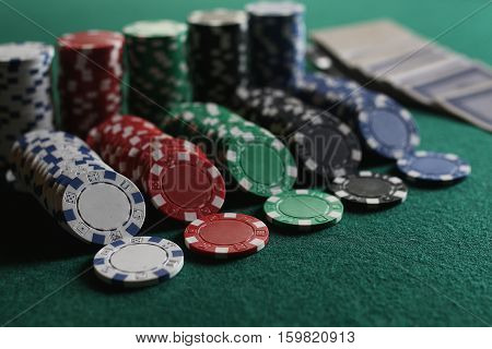 set of chips and cards on a green baize gambling casino