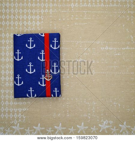 Beautiful small notebook in ship anchor design cover with red ribbon closure lying on vintage paper. Copy space. Square composition.