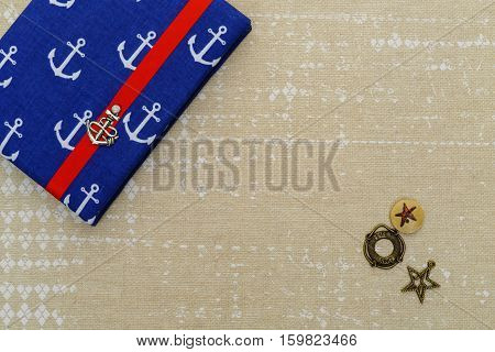 Beautiful small notebook in ship anchor design cover with red ribbon closure lying on vintage paper. Copy space.