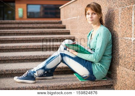 Portrait of a beautiful teenage student girl sitting on stairs in park with copy book and studing. Sunny summer day. Modern and casual lifestyle. Woman with note pad.