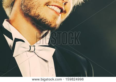 Elegance masculinity elegance success concept. Smiling man wearing dark tuxedo and bow tie close up studio shot on black background