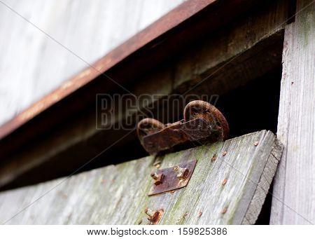 Rusty metal barn door wheeled slide mechanism on weathered barn wood