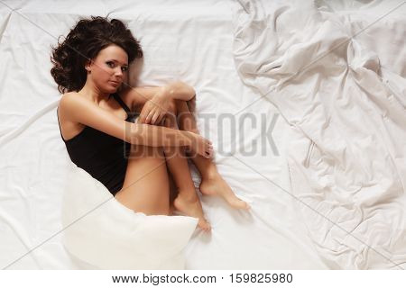 Sexy lazy girl in black body lying in fetal position on bed. Young lonely woman relaxing lazing in bedroom at morning.